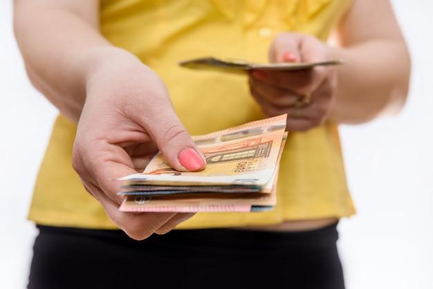 Mãos femininas segurando notas de euro de perto