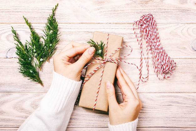 Mãos femininas segurando o ano novo ou natal presente plana leigos. modelo feriado celebração artesanal presente caixa e abeto árvore cones vista superior. toned