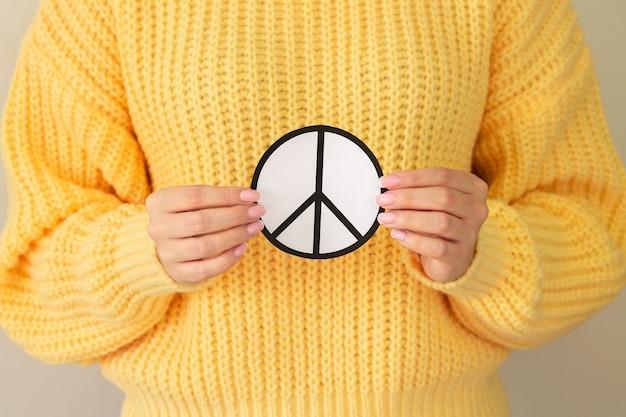 Mãos femininas segurando o símbolo da paz de papel. conceito de liberdade, amor e paz