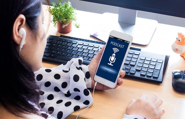 Mãos femininas, segurando o telefone móvel e ouvir podcast