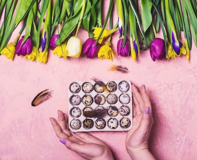 Mãos femininas segurando ovos de páscoa em uma superfície floral rosa