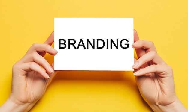 Mãos femininas segurando papel cartão com a marca de texto em um fundo amarelo. conceito de negócios e finanças