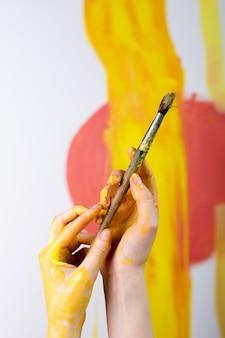 Mãos femininas segurando pincéis pintando um quadro em um cavalete