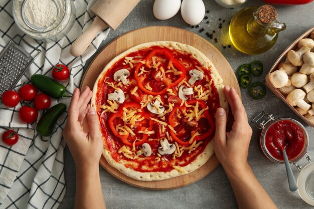 Mãos femininas segurando pizza crua em uma superfície cinza com ingredientes para cozinhar