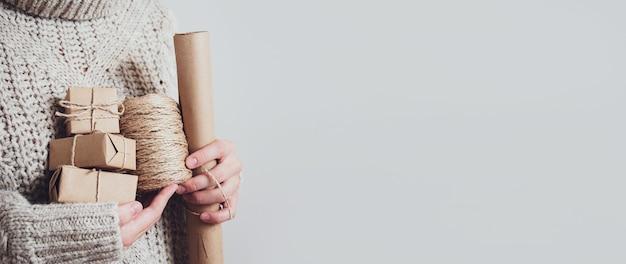 Mãos femininas segurando presentes, papel artesanal e corda, close-up, espaço de cópia.