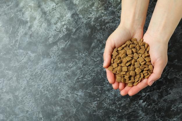 Mãos femininas segurando ração para animais de estimação na fumaça preta
