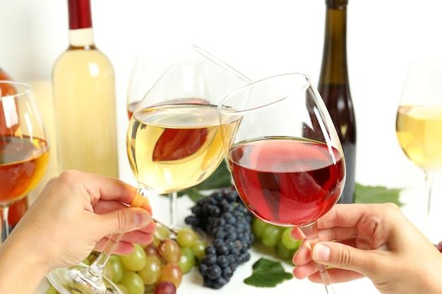 Mãos femininas segurando taças de vinho e um brinde, close-up