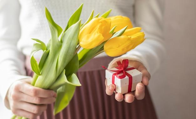 Mãos femininas segurando tulipas e caixa de presente no plano de fundo de escrita
