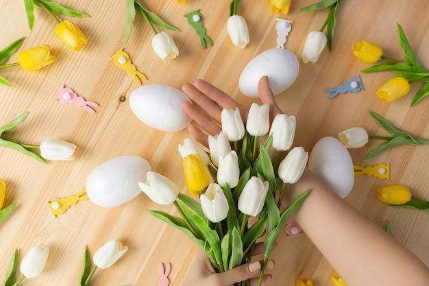Mãos femininas segurando um buquê de flores frescas de tulipa em um fundo rosa de madeira, composição plana leiga com espaço de cópia