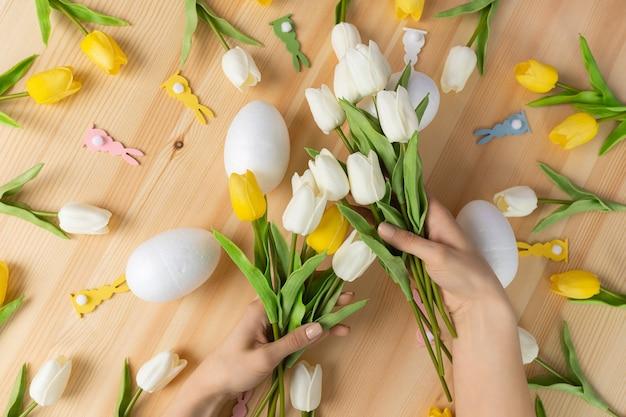Mãos femininas segurando um buquê de flores frescas de tulipas brancas em fundo de madeira, composição plana leiga com espaço de cópia