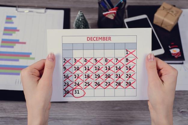 Mãos femininas segurando um calendário com a data de ano novo circulada