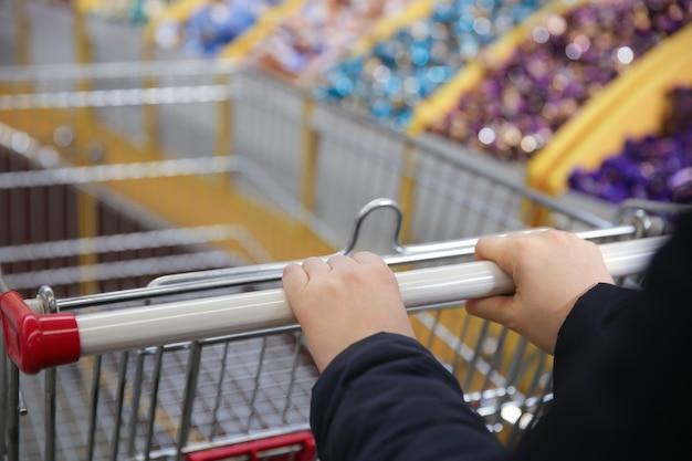 Mãos femininas segurando um carrinho de supermercado