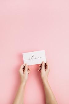 Mãos femininas segurando um cartão com citação caligráfica i love u em fundo rosa pálido. flat lay, top view conceito de amor.