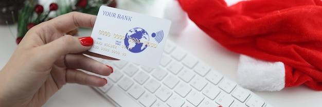 Mãos femininas segurando um cartão de crédito do banco perto do teclado e chapéu de papai noel e árvore de natal.