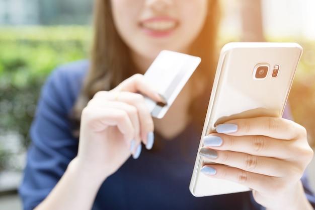 Mãos femininas segurando um cartão de crédito