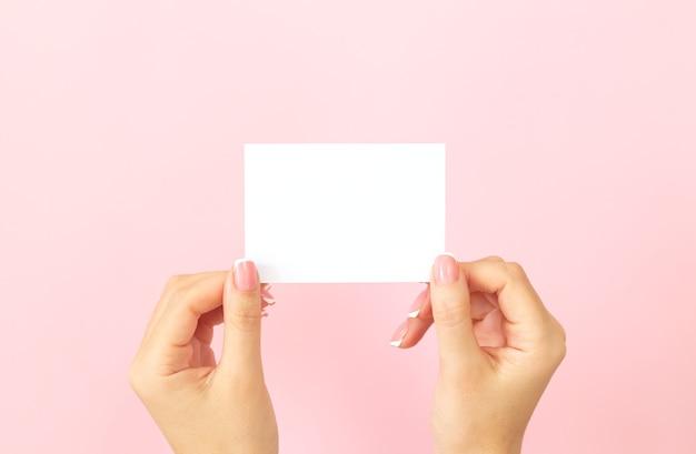 Mãos femininas segurando um cartão de visita branco em branco, desconto ou folheto sobre fundo rosa
