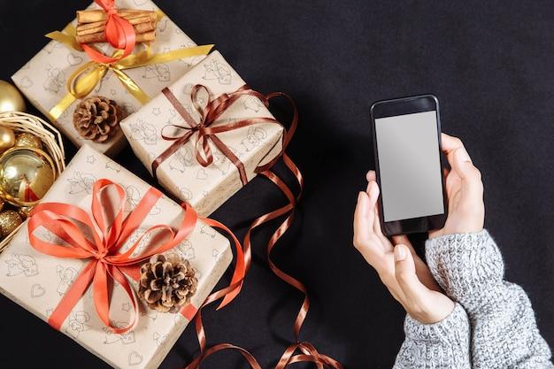 Mãos femininas segurando um celular em branco com presentes de natal