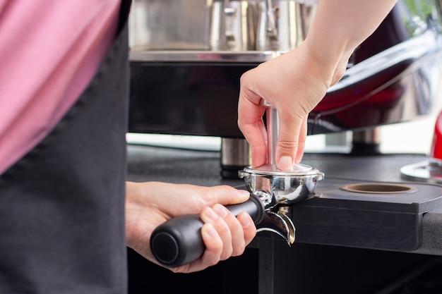 Mãos femininas segurando um compactador de metal