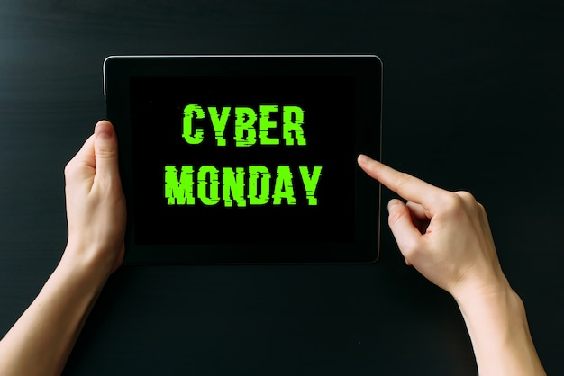 Mãos femininas segurando um computador tablet com inscrição na tela contra a mesa de madeira preta, close-up. conceito de cyber segunda-feira.