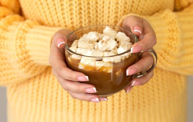Mãos femininas segurando um copo de chocolate quente ou café com close-up de marshmallow