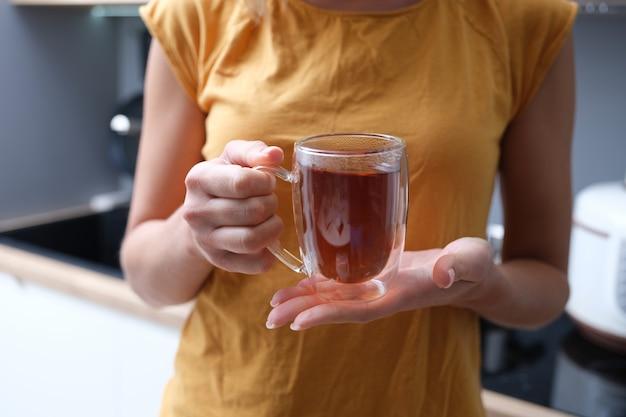 Mãos femininas segurando um copo transparente com chá closeup