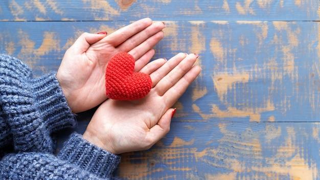 Mãos femininas segurando um coração vermelho de malha artesanal. vista do topo