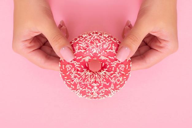 Mãos femininas segurando um donut de morango