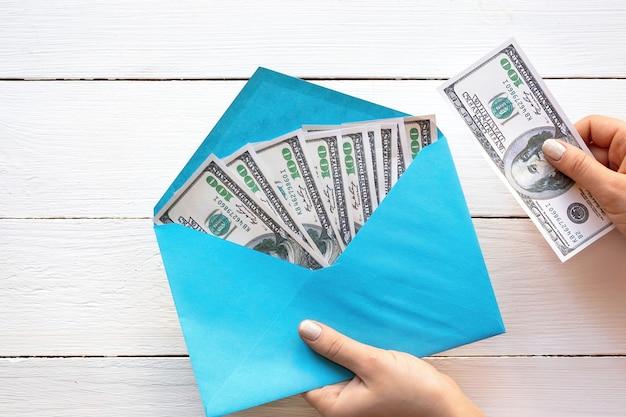 Mãos femininas segurando um envelope com dinheiro, fundo de madeira. ideia de finanças