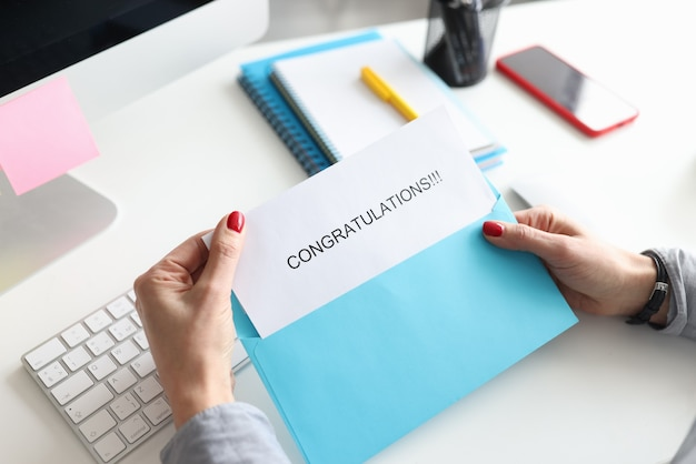 Mãos femininas segurando um envelope com parabéns closeup