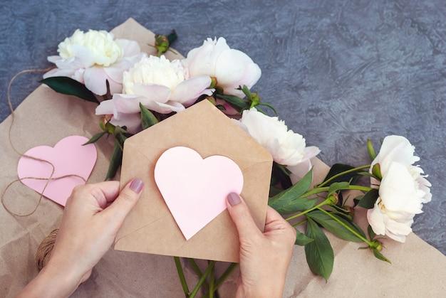 Mãos femininas segurando um envelope com um coração de papel rosa, enviando flores e um convite para um evento romântico
