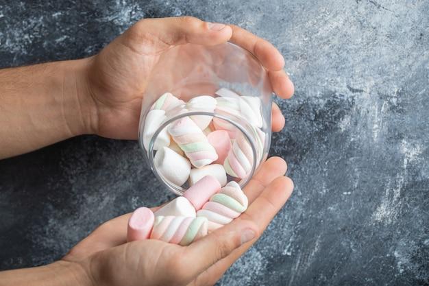 Mãos femininas segurando um frasco de vidro de marshmallows no fundo de mármore
