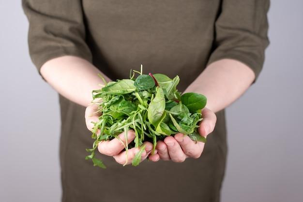 Mãos femininas segurando um monte de vegetais folhosos em um gramado