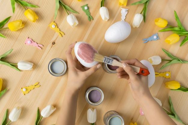 Mãos femininas segurando um pincel, pintando ovos de páscoa no fundo da mesa de madeira, composição plana leiga