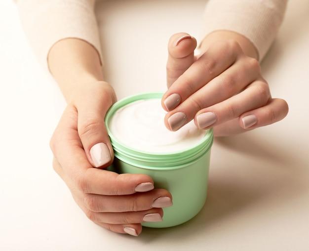 Mãos femininas segurando um pote de creme branco