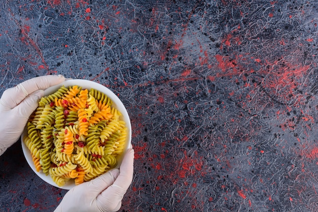 Mãos femininas segurando um prato branco de massa fusilli multicolorida crua e seca em uma superfície escura