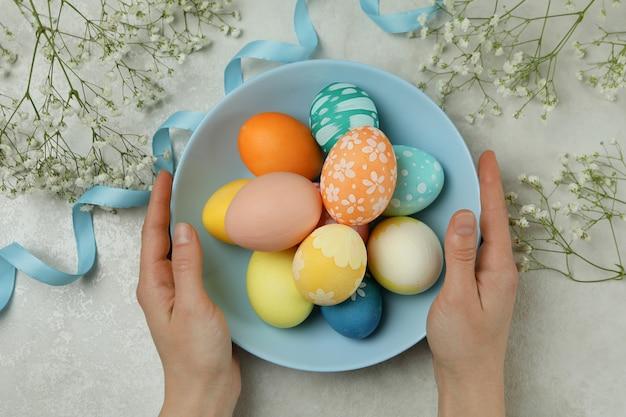Mãos femininas segurando um prato de ovos de páscoa coloridos, vista de cima