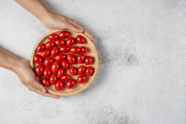 Mãos femininas segurando um prato de tomate cereja.