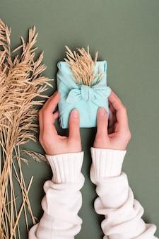 Mãos femininas segurando um presente de furoshiki ecológico com espigas de grama seca em fundo verde