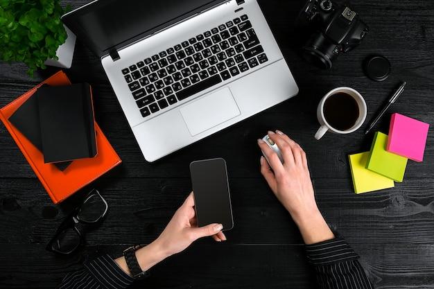 Mãos femininas segurando um smart e digitando no teclado de um laptop na mesa de madeira preta.