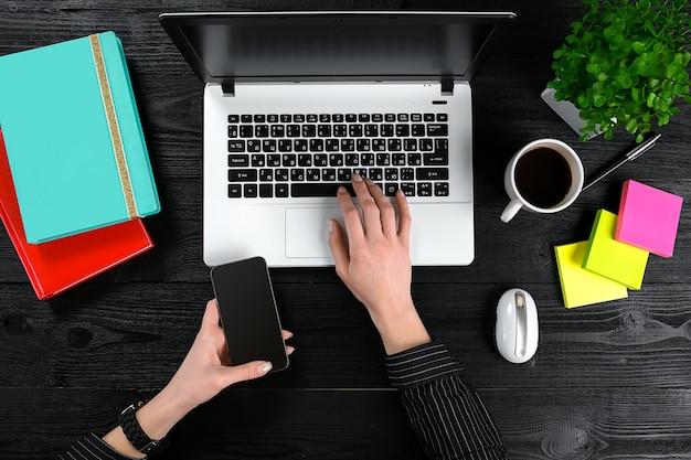 Mãos femininas segurando um smart e digitando no teclado de um laptop na mesa de madeira preta