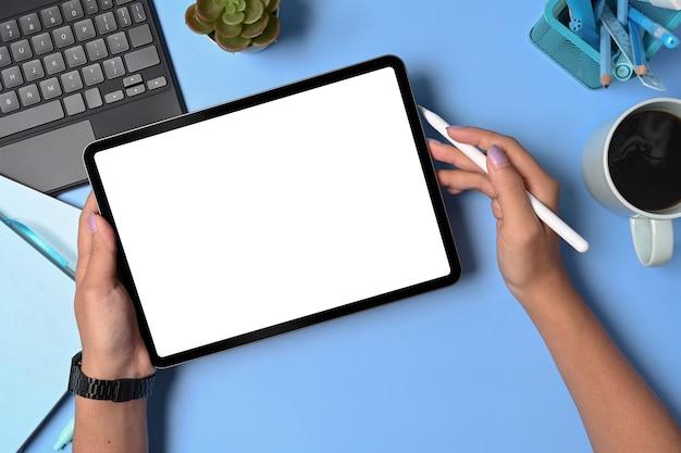 Mãos femininas segurando um tablet digital com tela em branco e caneta stylus.
