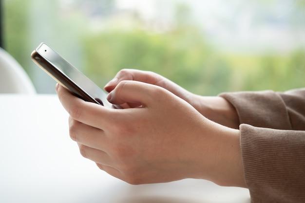 Mãos femininas segurando um telefone celular enquanto está sentado em um café perto da janela