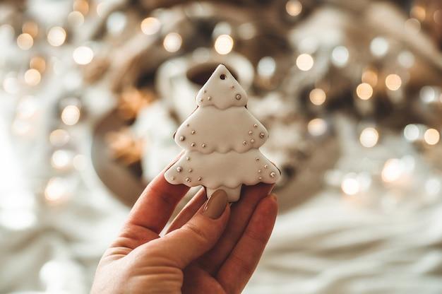 Mãos femininas segurando uma árvore de natal em formato de biscoito
