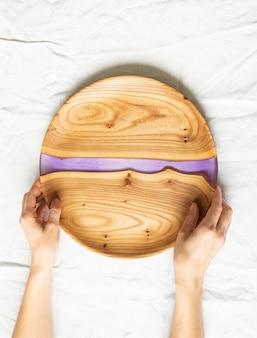 Mãos femininas segurando uma bandeja redonda de madeira com uma inserção de resina lilás
