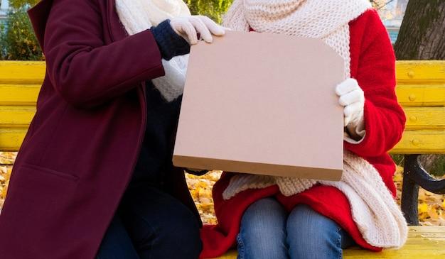 Mãos femininas segurando uma caixa de embalagem com pizza