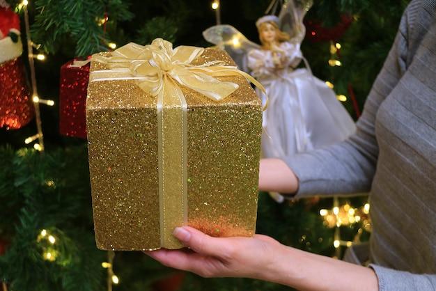 Mãos femininas segurando uma caixa de ouro com glitter dourados e enfeites de natal