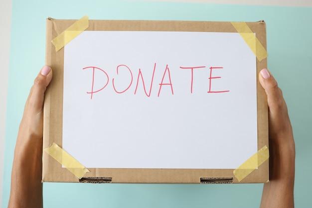 Mãos femininas segurando uma caixa de papelão com a inscrição donate closeup
