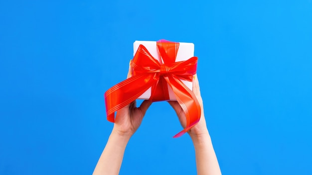 Mãos femininas segurando uma caixa de presente com fita vermelha