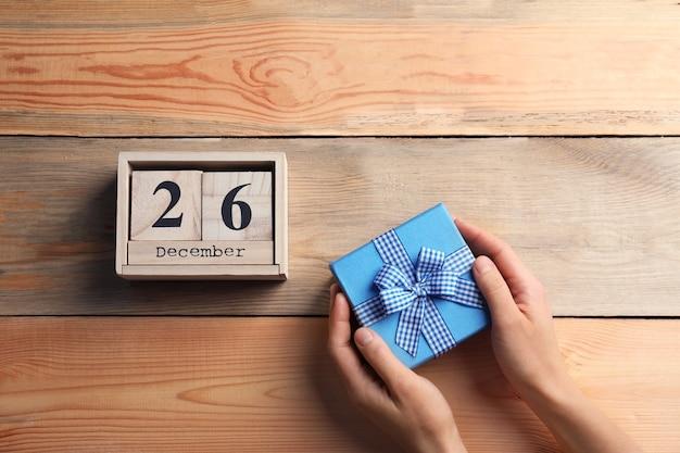 Mãos femininas segurando uma caixa de presente e um calendário com data em fundo de madeira. conceito de natal
