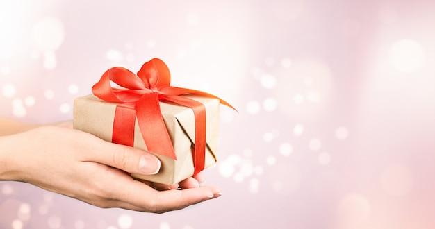 Mãos femininas segurando uma caixa de presente na parede rosa desfocada